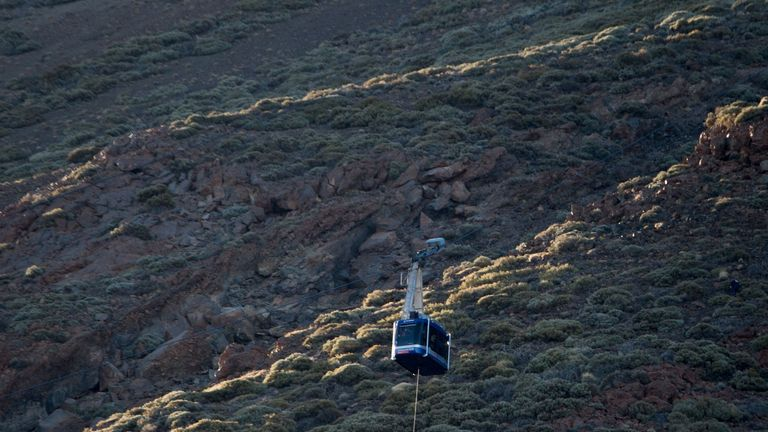 A person hangs from a rope beneath a cable car booth after 60 tourists became trapped i