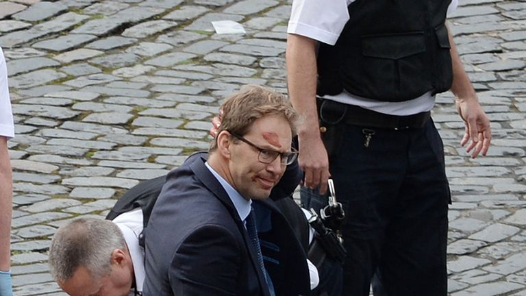 Conservative MP Tobias Ellwood stands amongst the emergency services at the scene outside the Palace of Westminster