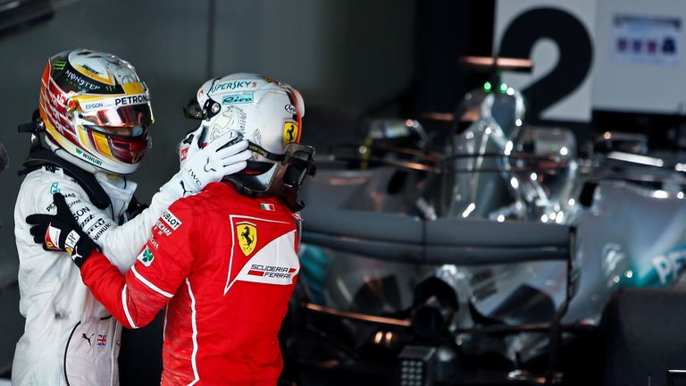 Vettel is congratulated by Mercedes driver Lewis Hamilton