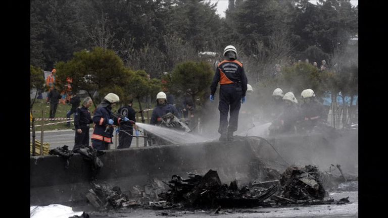 Firefighters douse the charred remains of the aircraft