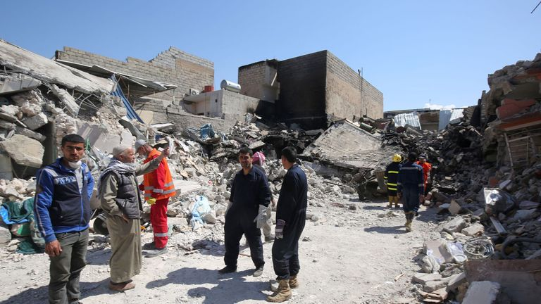 Iraqi citizens and rescue workers inspect the damage in the Mosul al-Jadida area on March 26, 2017, following air strikes in which civilians have been reportedly killed during an ongoing offensive against the Islamic State (IS) group. Iraq is investigating air strikes in west Mosul that reportedly killed large numbers of civilians in recent days, a military spokesman said