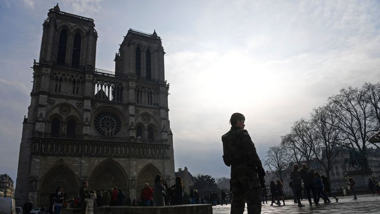 A soldier stands guard by Notre Dame Cathedral