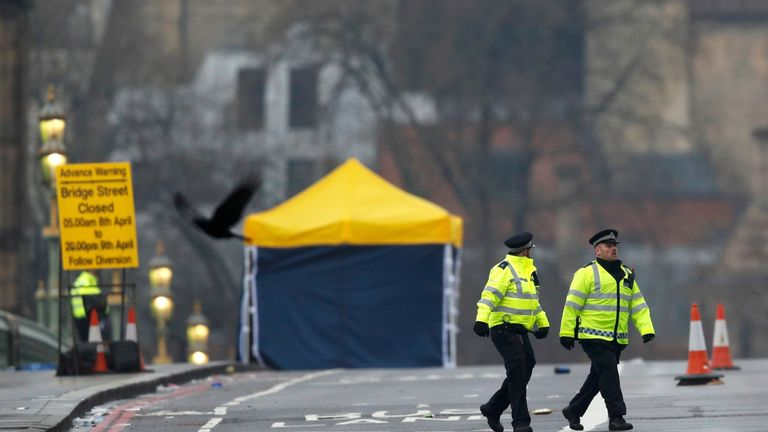 Police officers walk across Westminster Bridge the morning after the attack