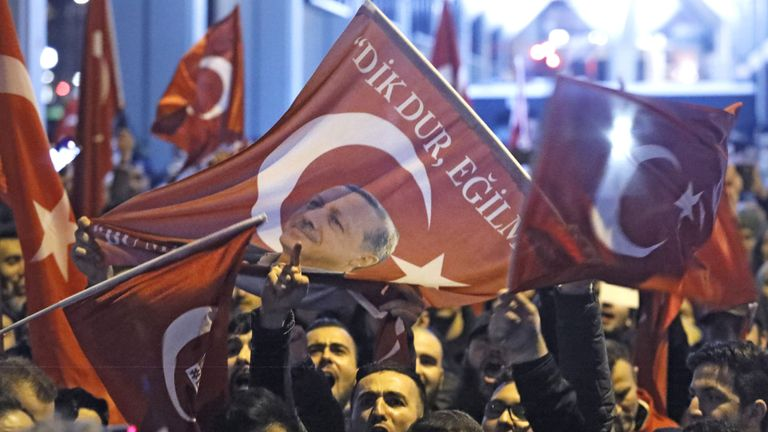Demonstrators with banners of Turkish President Recep Tayyip Erdogan gather outsidethe Turkish consulate
