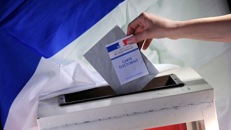 A voter prepares to cast their vote in the French elections