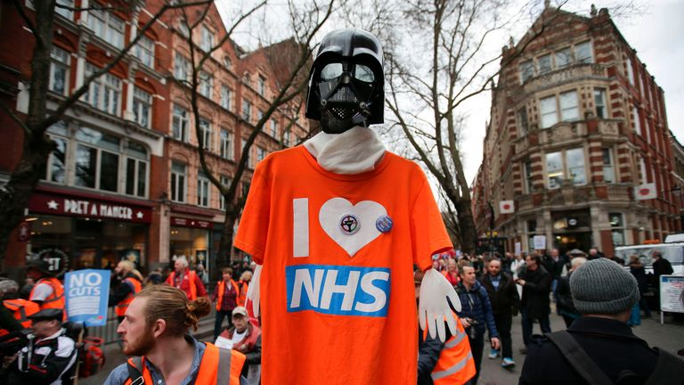 A protester holds a Star Wars themed T-Shirt-placard during a march against private companies' involvement in the National Health Service (NHS) and social care services provision and against cuts to NHS funding in central London on March 4, 2017