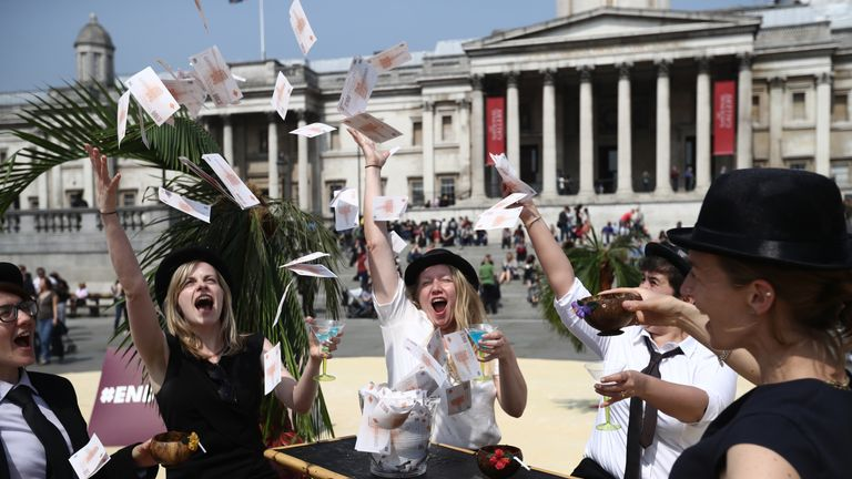 Protesters throw fake money as they take part in a demonstration against tax havens on May 12, 2016 in London, England