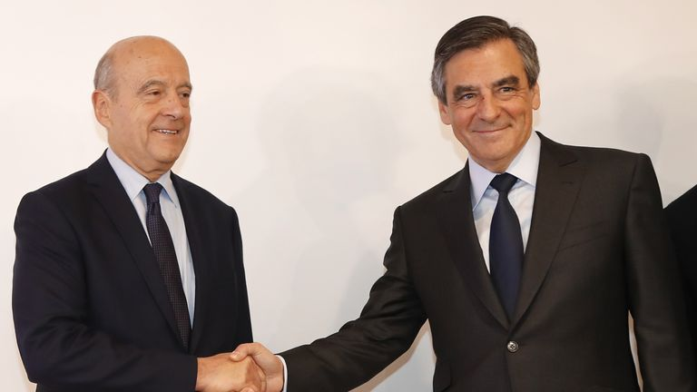 Francois Fillon shakes hands with former French Prime Minister Alain Juppe