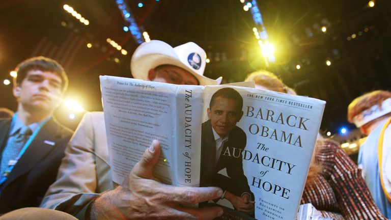A man reads a copy of Barack Obama's book The Audacity of Hope