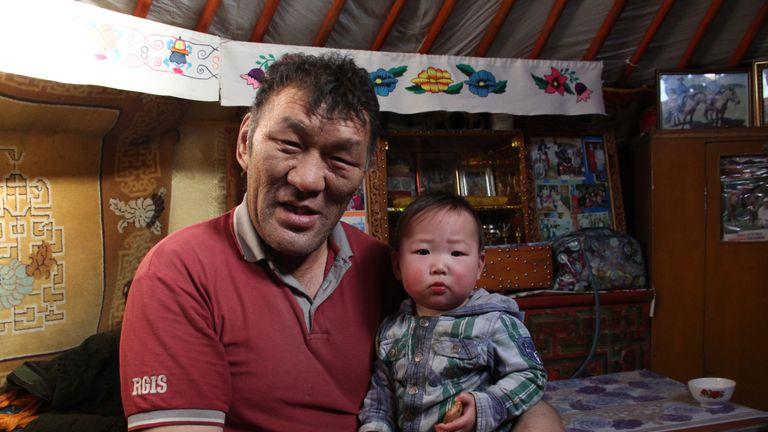 Herder Baatarkhuu Tserenbaljir with his 11-month-old grandson