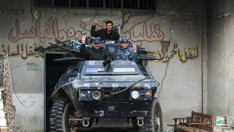 Iraqi forces flash the victory sign after advancing into the Old City in western Mosul
