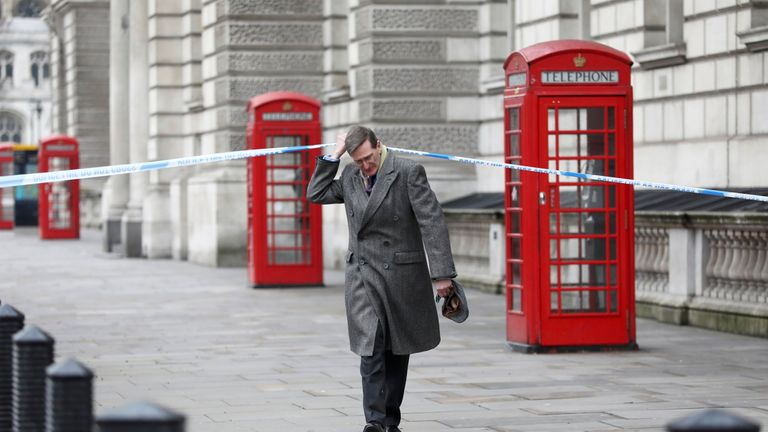 Conservative MP Dominc Grieve ducks under police tape on Whitehall