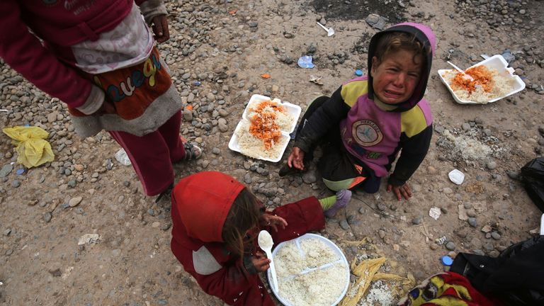 Iraqi children displaced from the city of Mosul eat food following their arrival at a camp in the Hamam al-Alil area south of the embattled city of Mosul