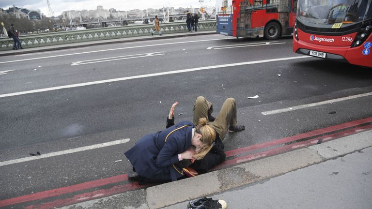 A woman helps an injured person on Westminster Bridge