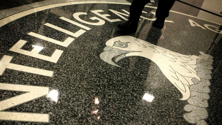 A man walks across the seal of the Central Intelligence Agency