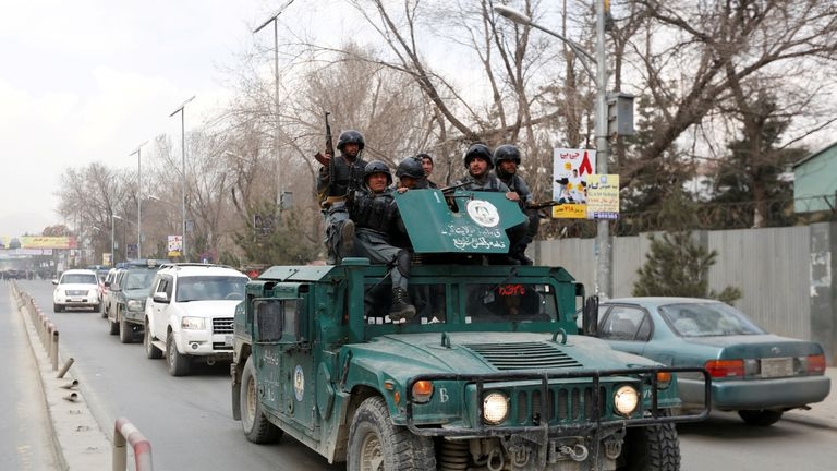 Afghan policemen arrive at the scene after a military hospital in Kabul comes under attack