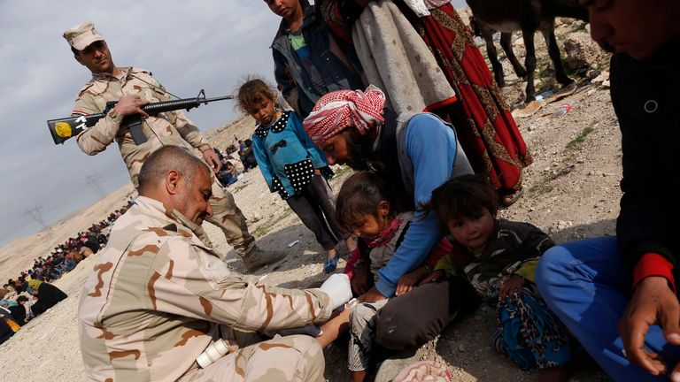 An Iraqi soldier treats a wounded child amid displaced civilians northwest of Mosul