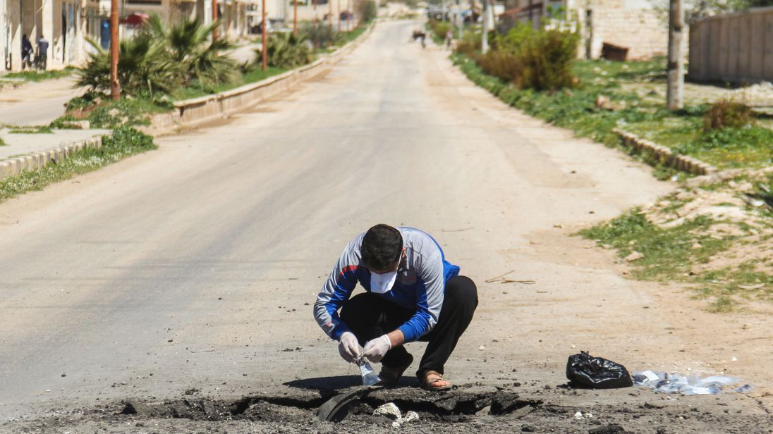 A Syrian man collects samples from the site of a suspected toxic gas attack