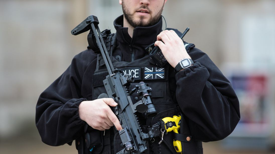 An armed police officer stands guard on Whitehall following the Westminster attack