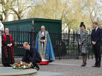 Prince William lays a wreath as Kate and Harry stand nearby