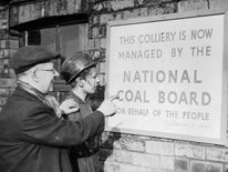 Two miners reading a notice announcing that their colliery is.. 'Now managed by the National Coal Board on behalf of the People'
