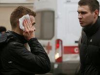 An injured person stands outside Sennaya Ploshchad metro station following explosions in St. Petersburg