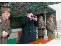 Kim Jong-Un smiles as he watches the action