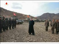 Kim Jong-Un stands in front of the tanks taking part in the competition