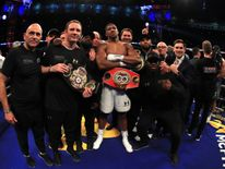 Joshua celebrates with his team following his victory