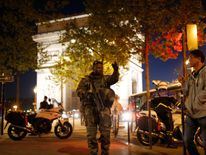 An armed soldier secures a side road near the Champs Elysees