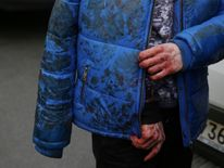 An iniured person walks outside Sennaya Ploshchad metro station following explosions