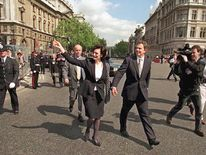 Tony Blair walks with his wife Cherie as they leave Downing Street on their way to the Palace of Westminster for the State Opening of Parliament