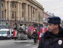 Members of Emergency services stand next to helicopter outside Tekhnologicheskiy institut metro station in St. Petersburg