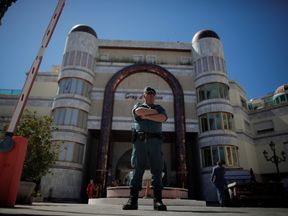 A Spanish civil guard officer stands outside one of Rifaat al Assad's seized buildings