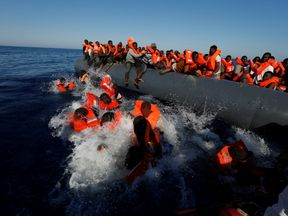 Migrants try to stay afloat after falling off their rubber dinghy