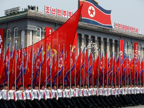 Men carry flags in front of the stand with North Korean leader Kim Jong Un