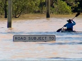 A kayaker paddles past a flood warning sign in New South Wales