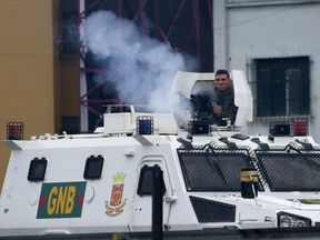 A riot police officer fires tear gas grenades from an armoured vehicle while clashing with demonstrators during a rally against Venezuela's President Nicolas Maduro in Caracas, Venezuela.