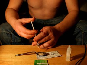 A heroin addict preparing to inject the drug. File pic