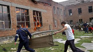 Two volunteers carry a stretcher as they approach the burning school