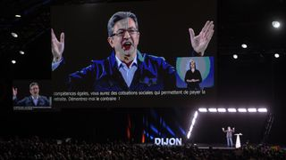 Jean-Luc Melenchon delivers a speech on stage in Dijon