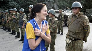 A woman cries in front of soldiers cordoning off the school building