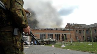 Soldiers and security forces in front of the burning school