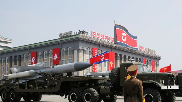 Missiles are driven past North Korean leader Kim Jong Un and other high ranking officials