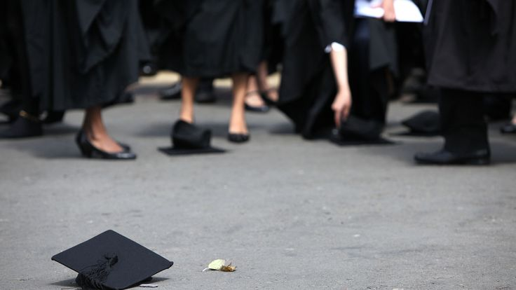 A mortar board lies on the ground after a graduation ceremony