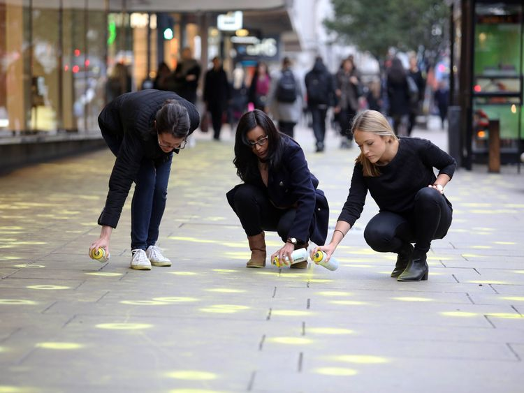 Ruth Pipkin, Lina Solanki and Natalie Merrix - representatives from The Chewing Gum Action Group (CGAG), highlight pieces of discarded gum, using fluorescent chalk, on the pavements of Oxford Street, London