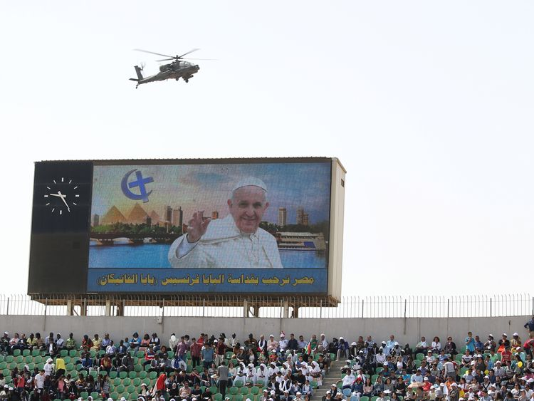 A military helicopter hovers overhead as Pope Francis leads a mass in Cairo