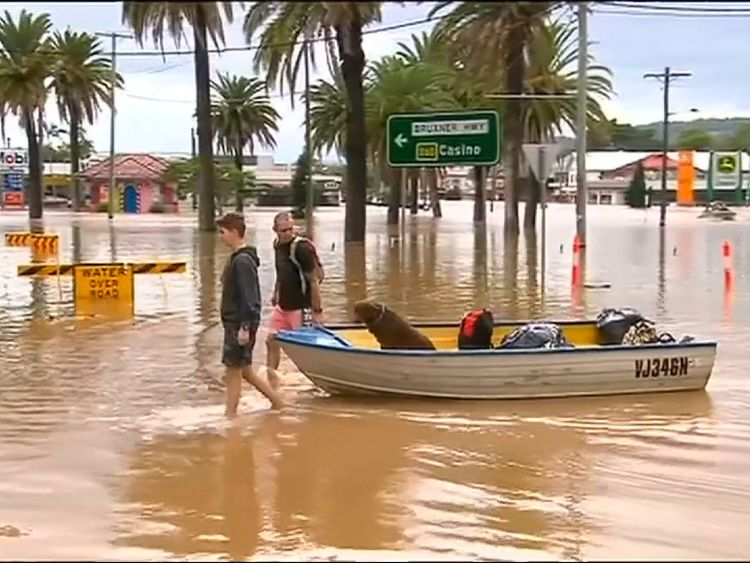 People use a boat to get through floodwaters in Lismore, New South Wales