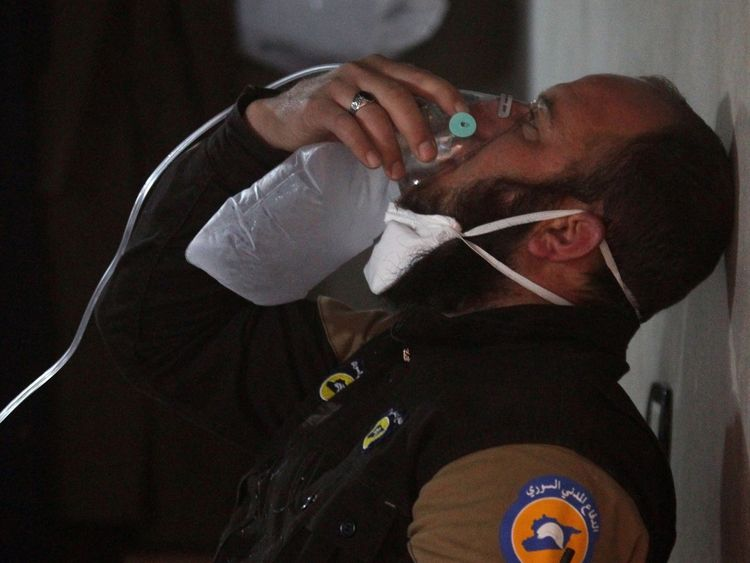 A rescue worker breathes through an oxygen mask after a 'chemical attack' in Idlib