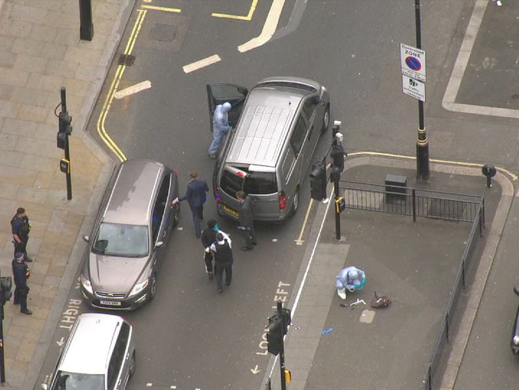 Aerial view of suspect being escorted to car by police.